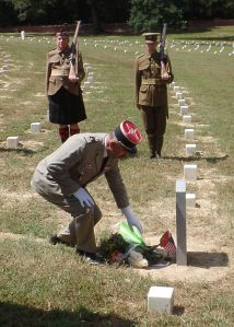 The French representative, Lieutenant Colonel Michel Comas, laying flowers at the grave